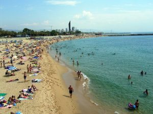 Nova Icaria beach in Barcelona with people lying on the sands