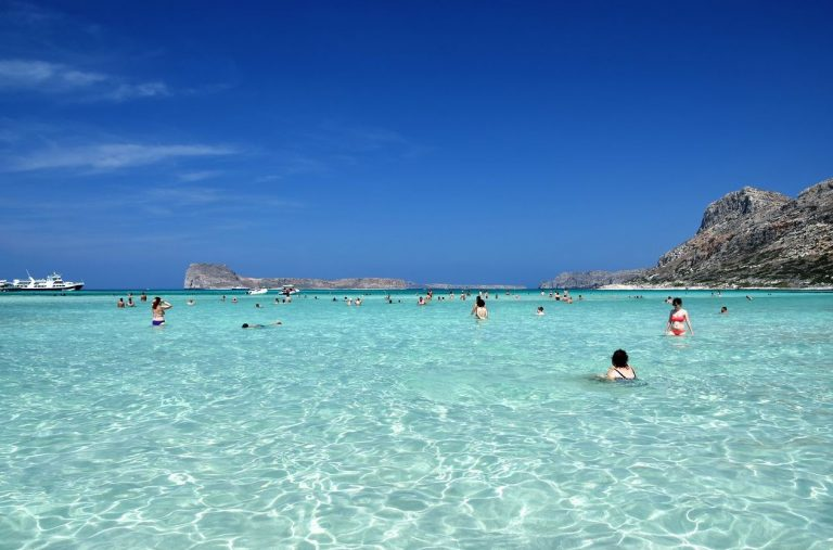 Vacationers swim on the beach of Balos