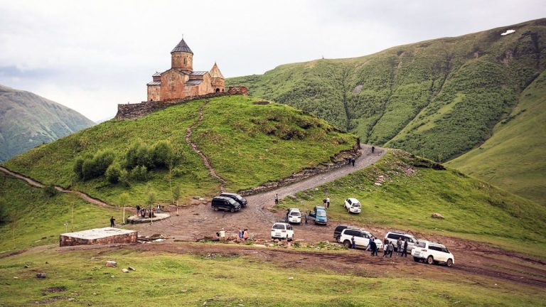 At the foot of the mountain are taxi drivers and cars of residents of Kazbegi.