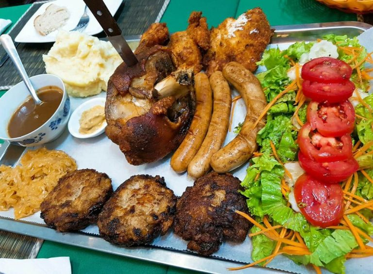 Knuckle, cutlets, sausages and side dish