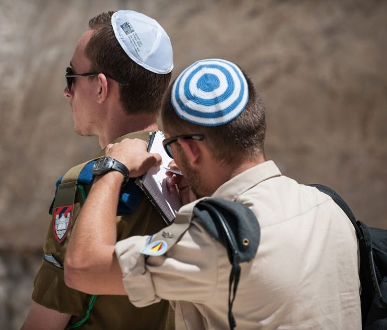 A soldier writes a note to the Kotel