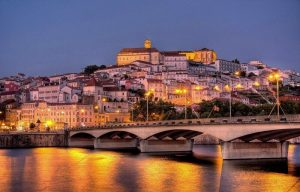 Coimbra at night with city lights reflecting on the river under the bridge